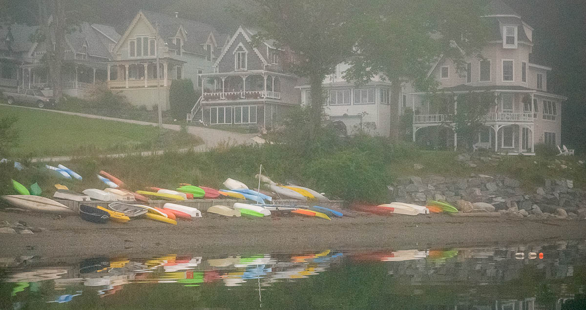 colorful kayaks rest on beach below row of victorian cottages on a foggy morning
