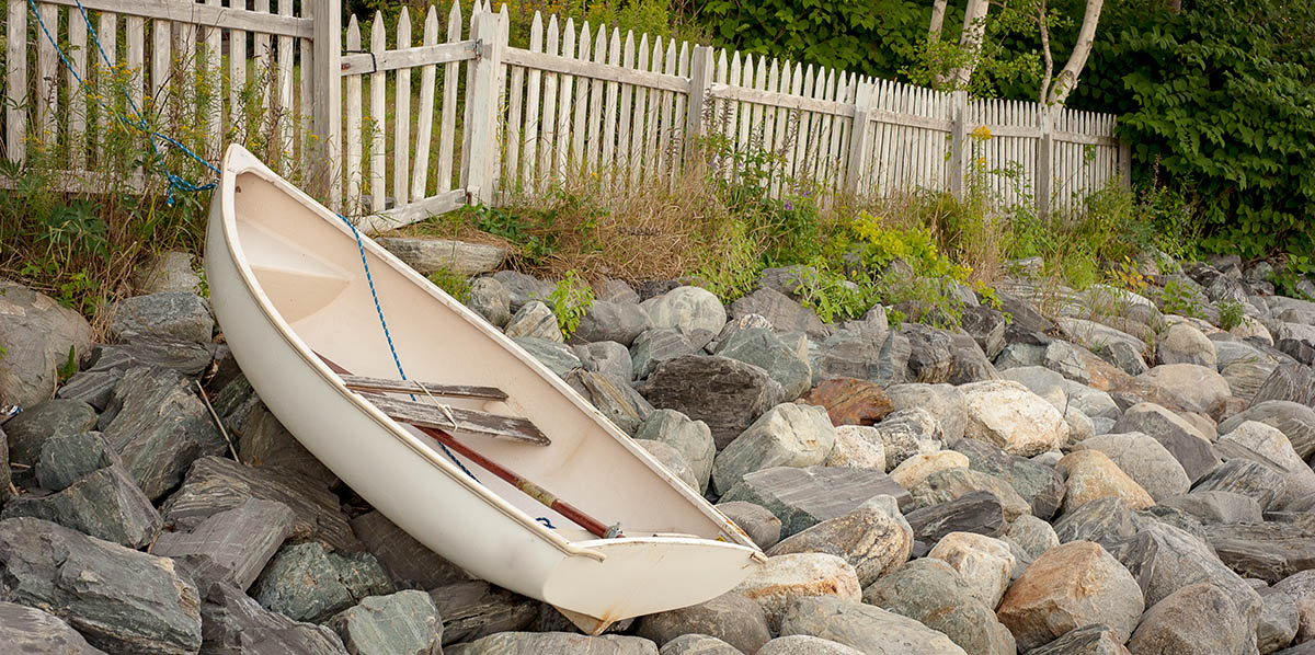 dinghy rests on a rocky Maine beach