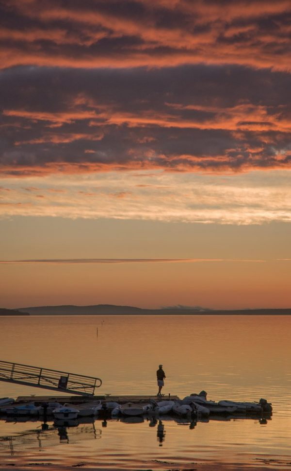 solitary fisherman on Bayside dock at dawn
