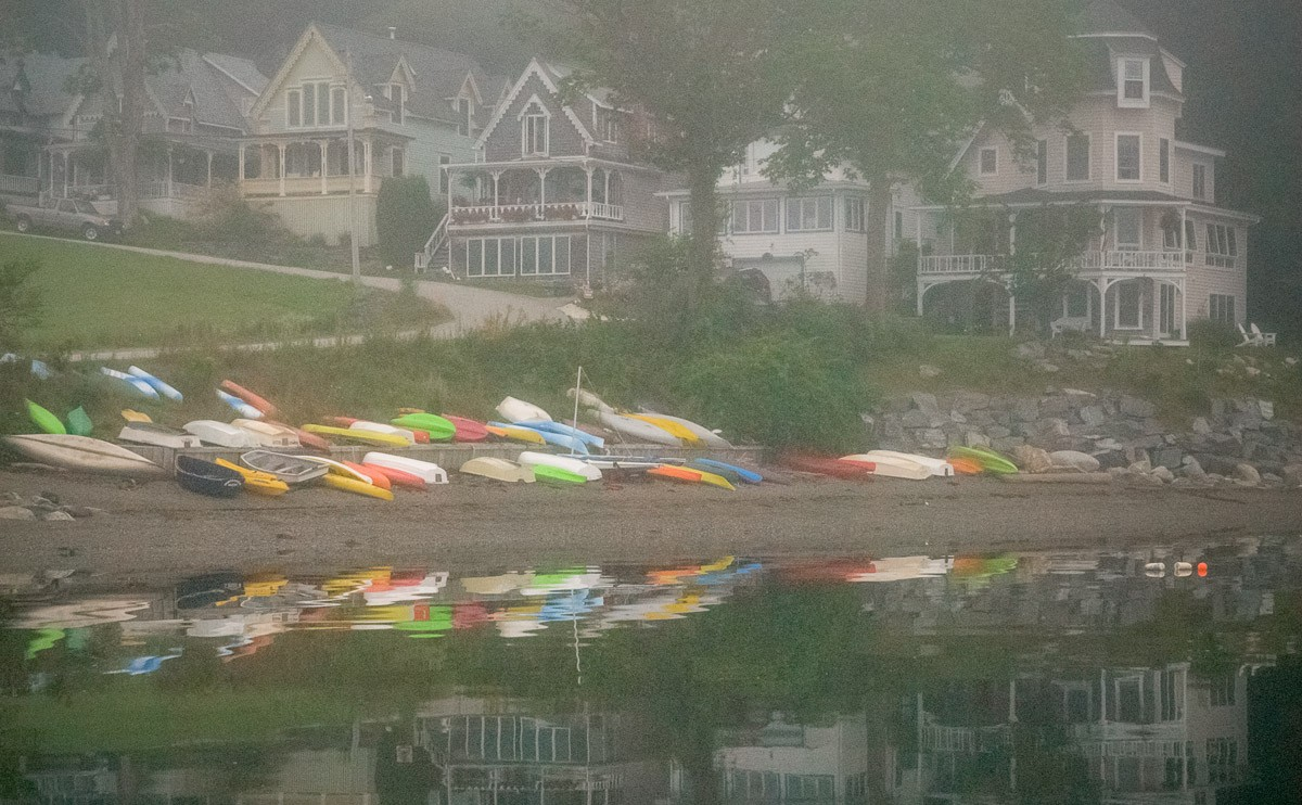 colorful kayaks and Victorian cottages reflected in bay on a foggy morning