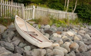 dinghy parked on rocky Maine seawall below a white picket fence