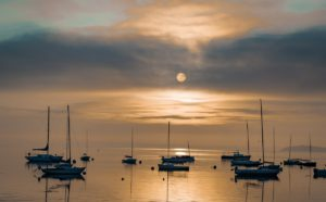 disk of sun filtered through morning clouds with sailboats at anchor below