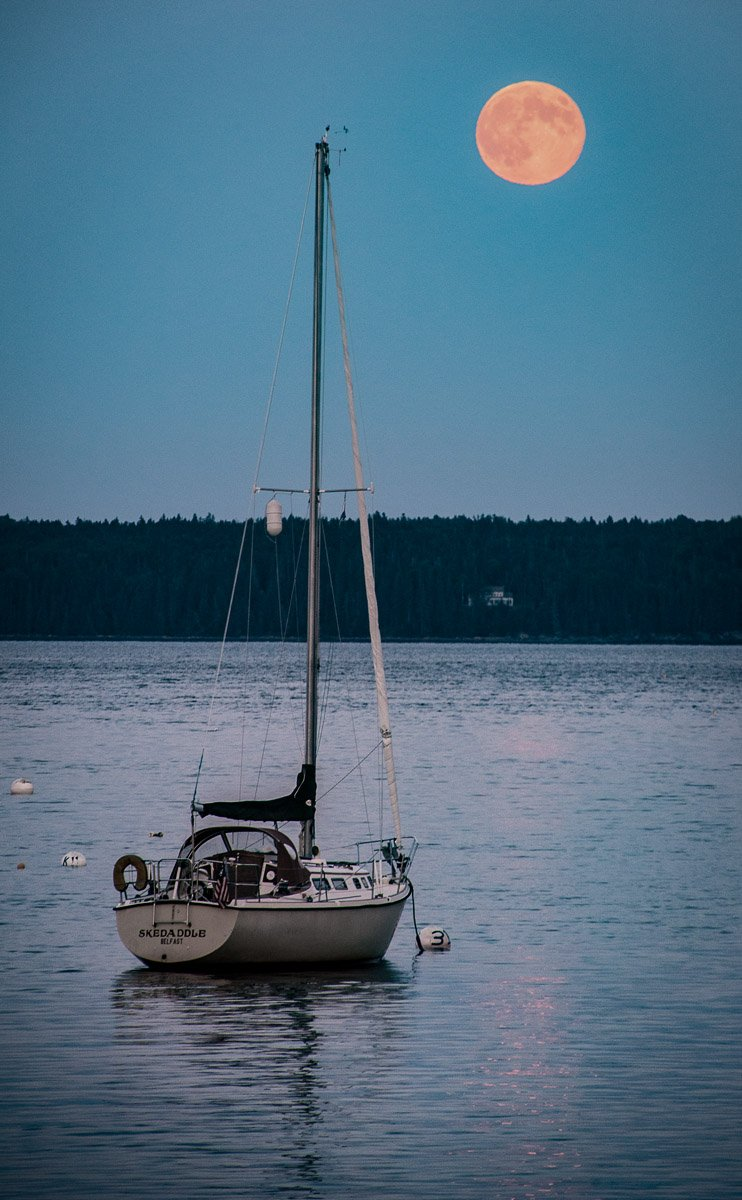 full moon rising over Islesboro with sailboat at anchor below