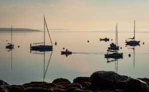 solitary sailor rows to his boat on still water early in the morning