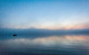 grainy image of solitary sailboat anchored in Bayside harbor, before sunrise