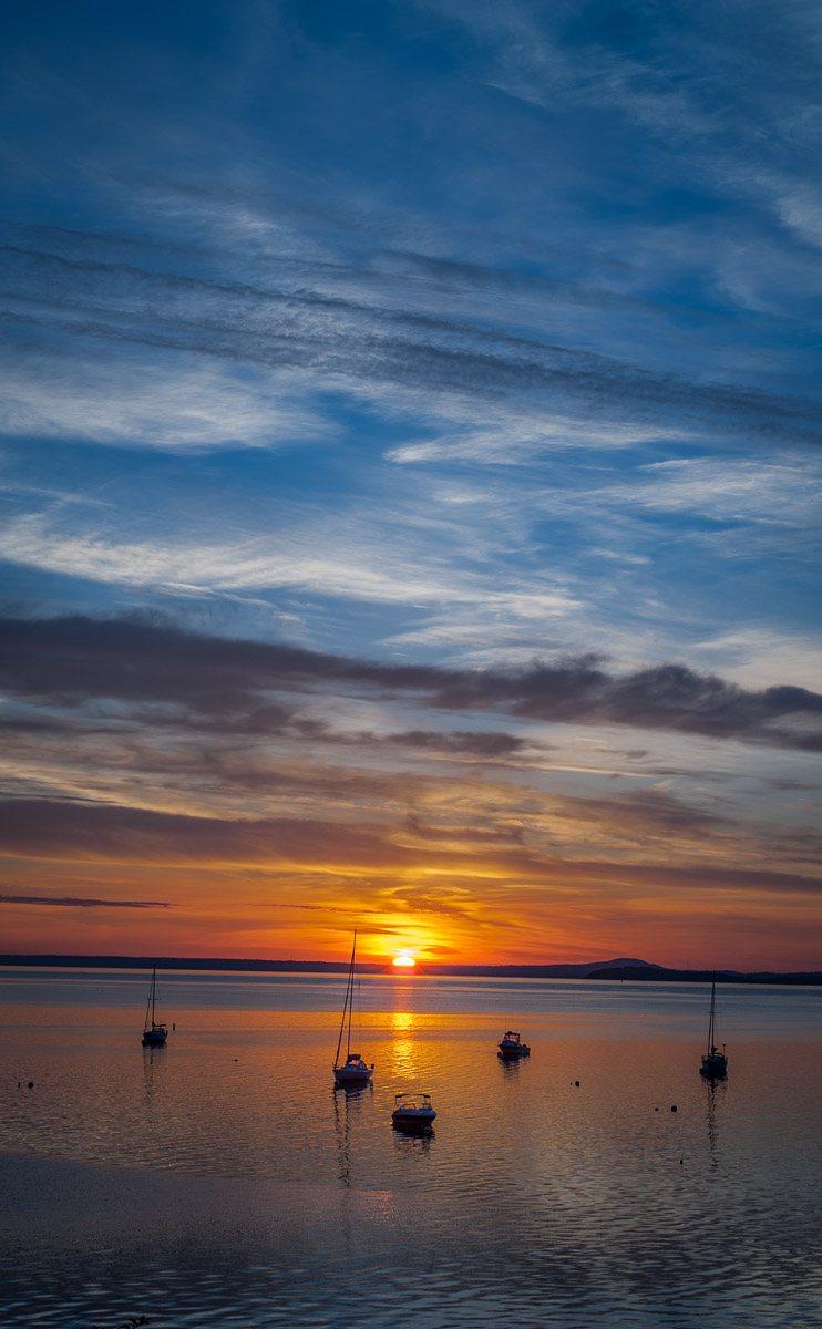 sun just clearing horizon behind boats at anchor, Bayside harbor