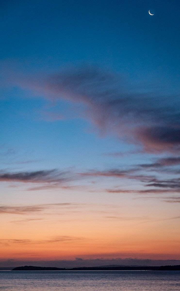 a sliver of a moon rides high above colorful pre-sunrise clouds