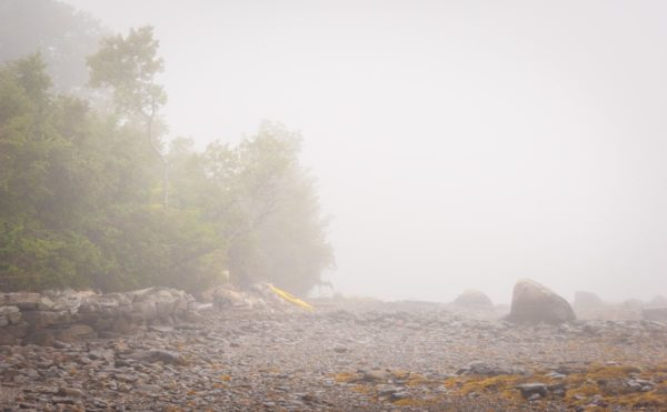yellow kayak rests on a rocky beach on a foggy morning in Maine