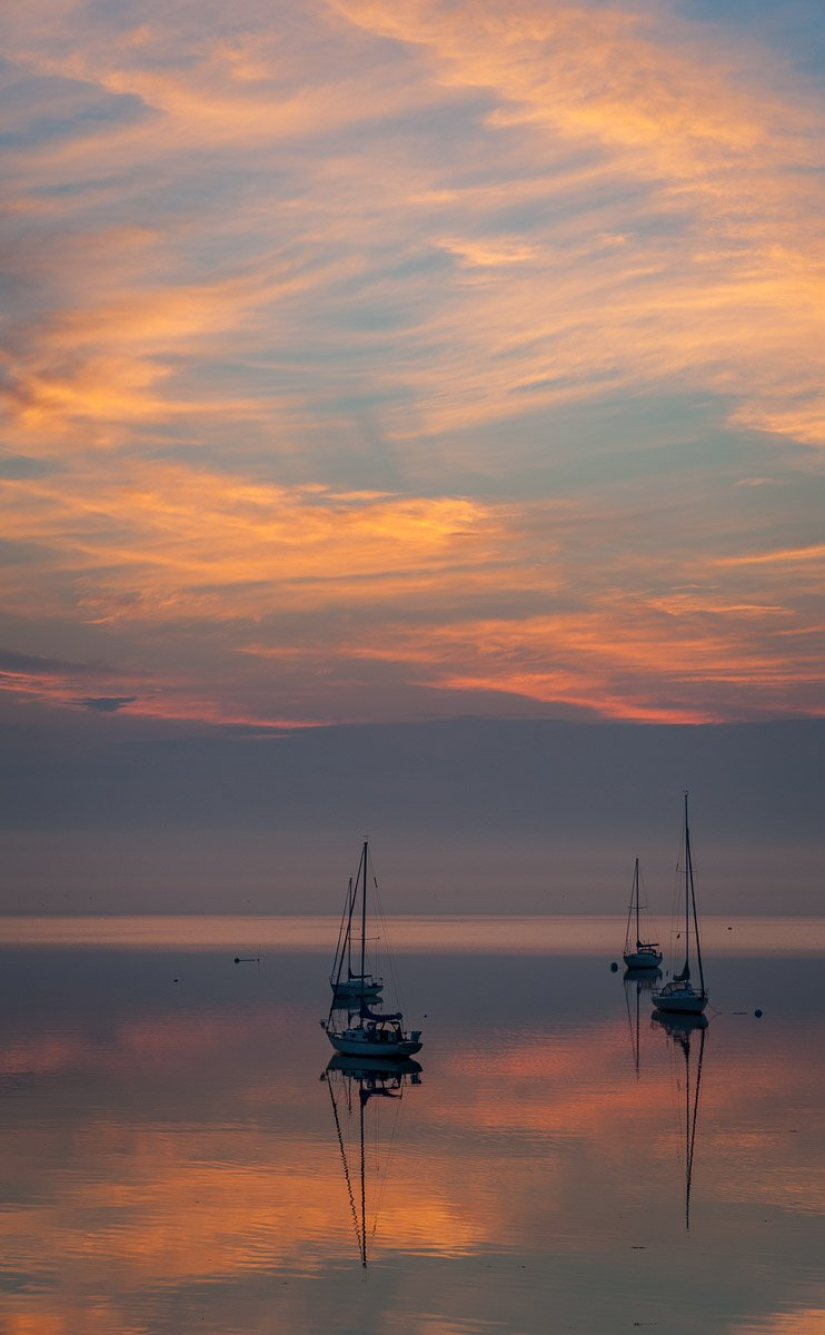 four sailboats at anchor on smooth water under colorful dawn clouds