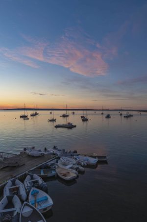 A cluster of dinghies at the Bayside dock, under a colorful dawn sky