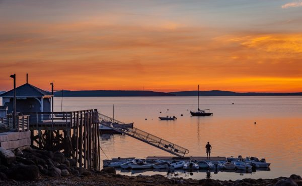 Solitary fisherman stands on the Bayside dock moments before sunrise