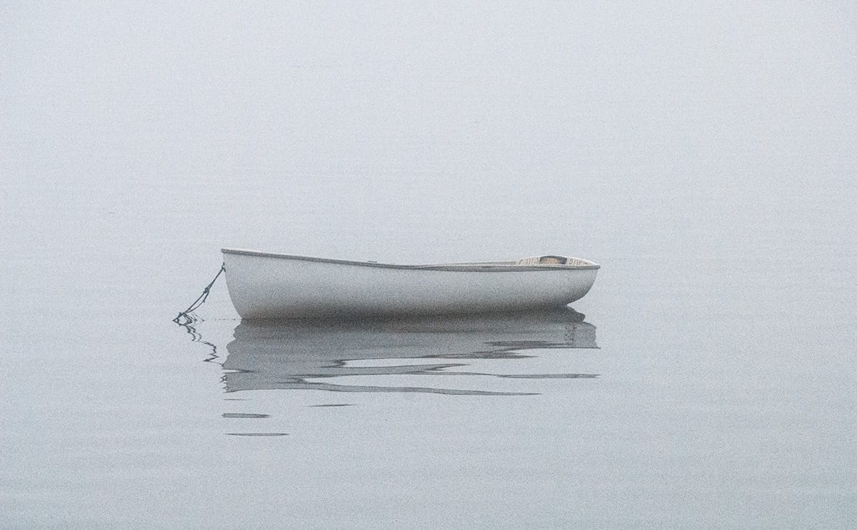 moored dinghy on a foggy day