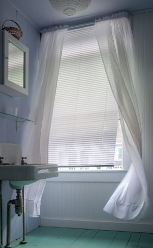 Sheer curtains blow in a summer breeze