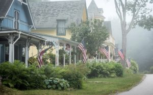 Row of summer cottages with American flags in foggy setting