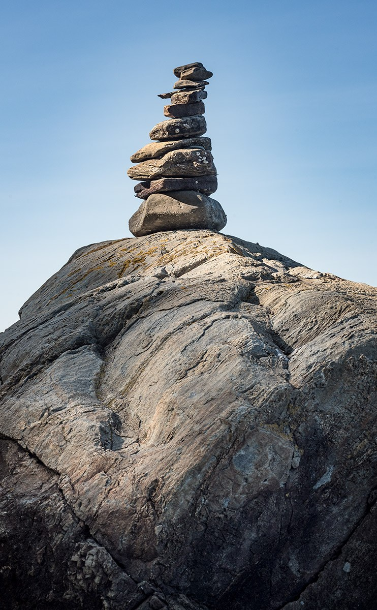 Small stone cairn built on top of a large boulder
