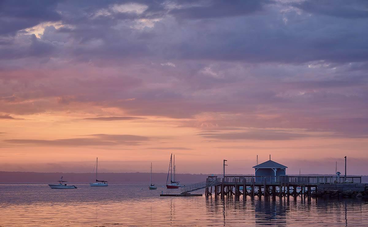 waterfront scene under cloudy dawn sky