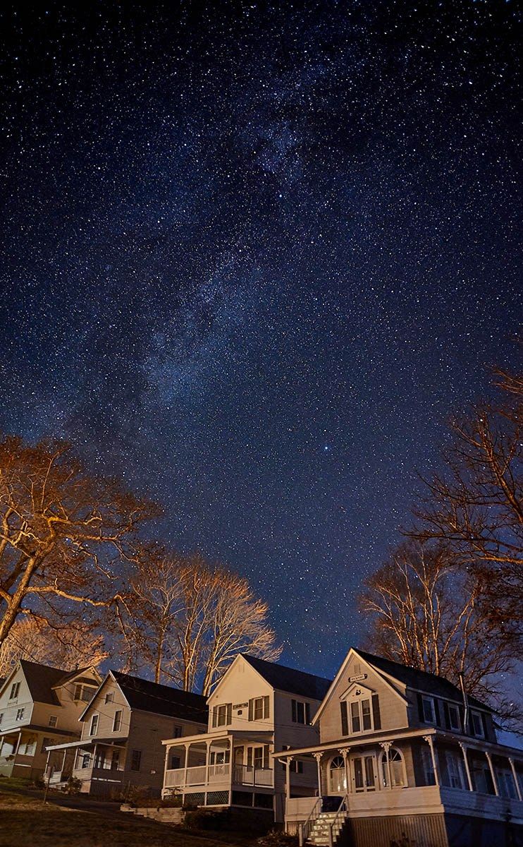 stars sweep over cottages on a clear night