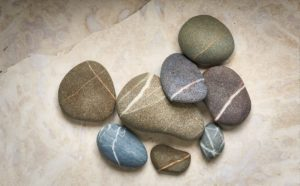 arrangement of striped beach stones on a stone background